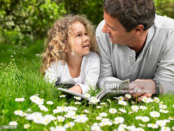Man and young girl lying in the grass reading and smiling.