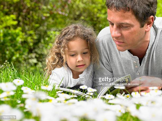 Man and young girl lying in the grass reading.