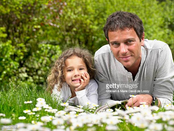 Man and young girl lying in the grass smiling.