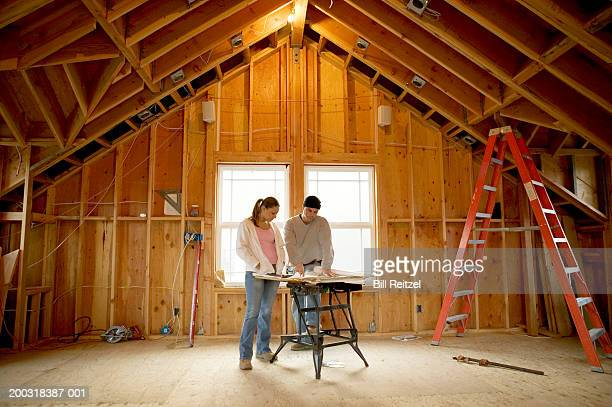 Man and young woman looking at blueprints in house under construction