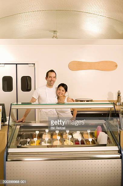 Man and young woman standing beside freezer in ice cream parlor