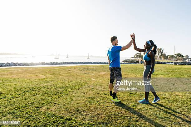 Man and young woman training, high fiving at coast, downtown San Diego, California, USA