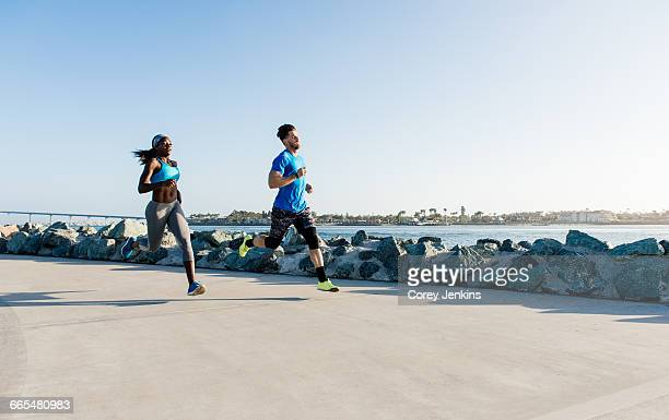 Man and young woman training, running on coast, downtown San Diego, California, USA