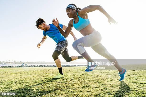 Man and young woman training, sprinting on coast, downtown San Diego, California, USA