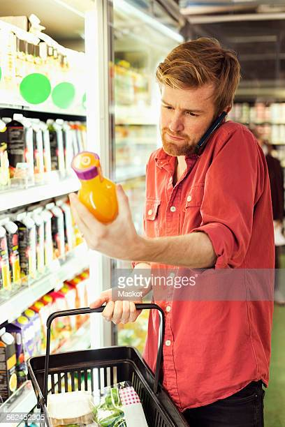 Man answering mobile phone while shopping juice bottle at freezer section in supermarket