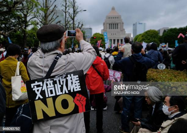 A man appeals 'NO Abe administration' during a demonstration in front of the National Diet building in Tokyo on April 14 2018 to demand the...