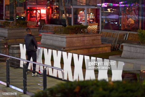 A man appears to urinate on a sign outside a bar in Manchester city centre northwest England ahead of new coronavirus restrictions coming into force...