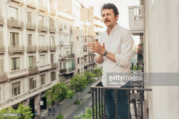 man applauding to the medical staff from the balcony for covid-19 - applauding stock pictures, royalty-free photos & images