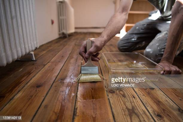 Man applies an oil treatment to protect a hardwood floor as part of self general renovation work in a house in Indre, outside Nantes, on August 21,...