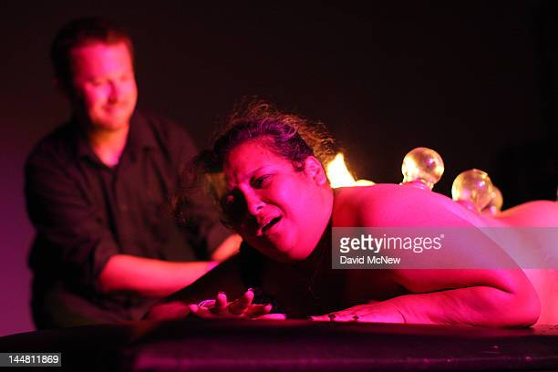 A man applies fire cups which suction onto the skin of a woman who is a willing submissive participant at a dungeon party during the DomConLA...