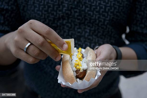 A man applies mustard to a vegan hot dog given by PETA on Capitol Hill for PETA's annual Congressional Veggie Dog Lunch on July 14 2016 in Washington...
