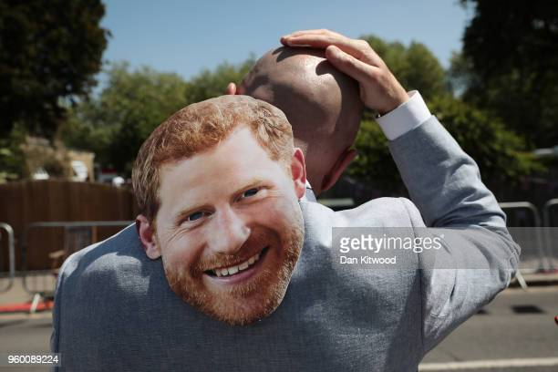 A man applies sun tan lotion too his head as he waits for the Prince Harry Duke of Sussex and Meghan Duchess of Sussex to process through Windsor in...