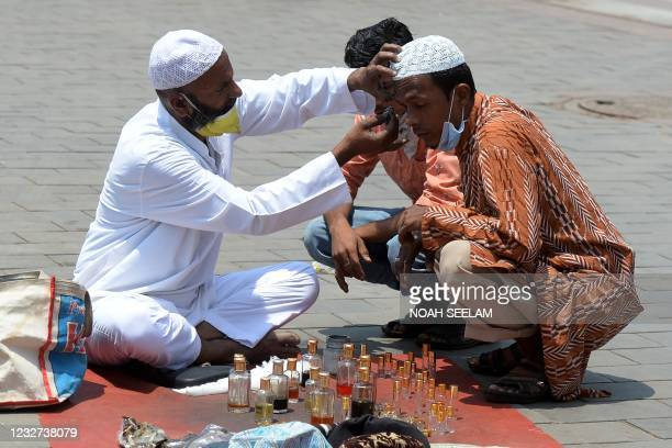 Man applies Surma-Kajal, a traditional eyeliner, on a Muslim devotee prior to offering Jummat-Ul-Vida prayers on the last Friday of the holy month of...