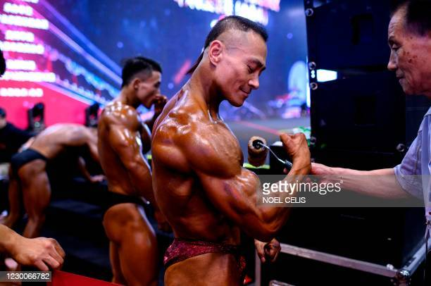 Man applies tanning lotion to a bodybuilder before going to the stage during the International Weightlifting Federation Beijing 2020 competition in...