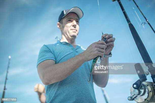 Man applying bait on fishing rod