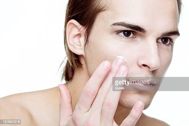 Man applying cosmetic cream on face