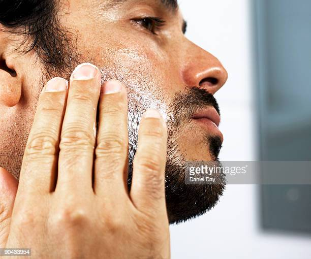 man applying cream to face - barba peluria del viso foto e immagini stock