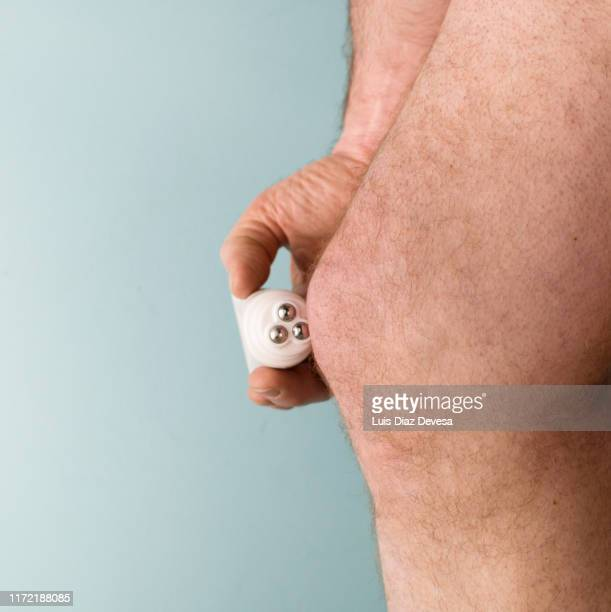 man applying cream with plastic massage tube with 3 roller ball applicator, for knee pain - off white stock pictures, royalty-free photos & images