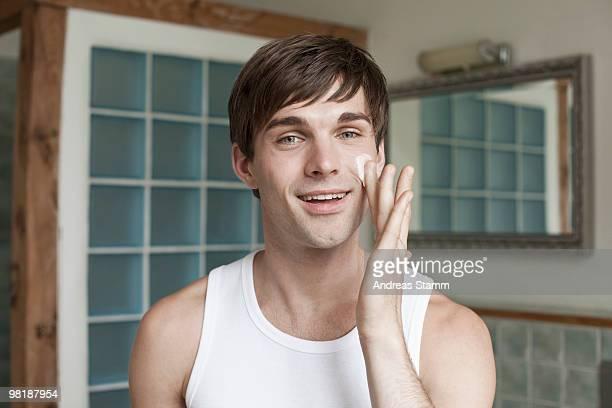A man applying face cream in the bathroom