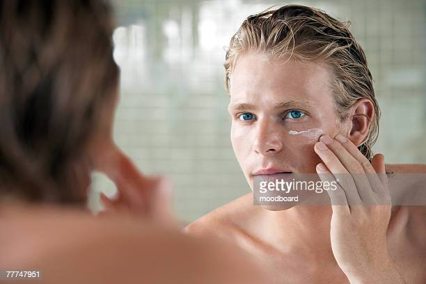 man applying facial cream - vanity mirror stock pictures, royalty-free photos & images