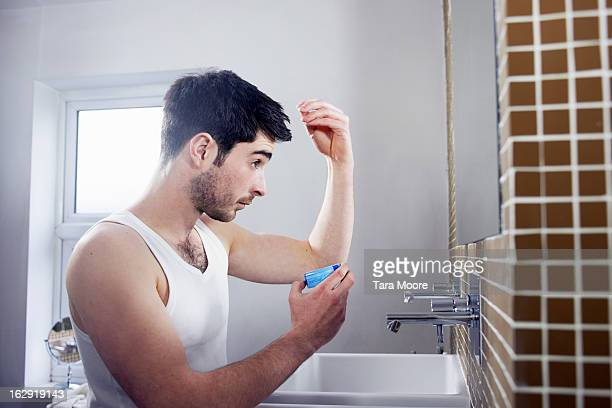 man applying gel to hair in bathroom