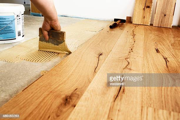 Man applying glue for laying finished parquet flooring, close-up