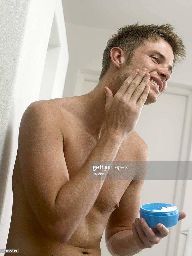 Man applying lotion : Stock Photo