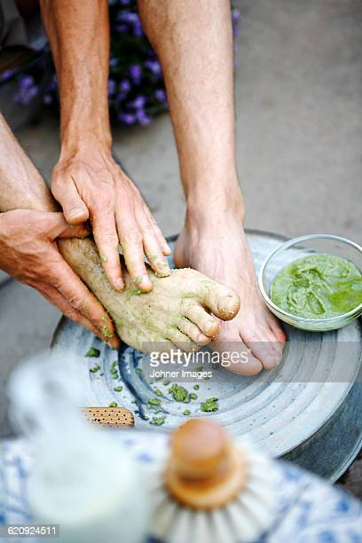 Man applying moisturizer on feet