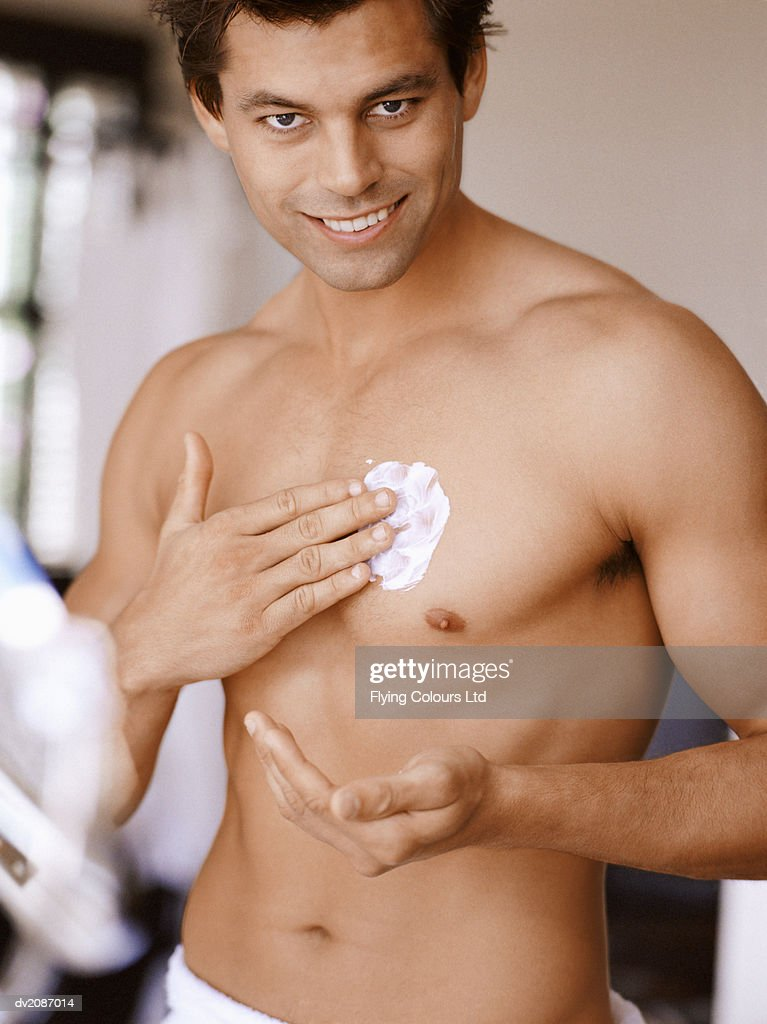 Man Applying Moisturizer on His Chest : Stock Photo