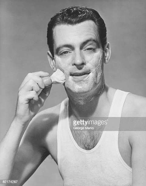 Man applying shave foam on face in studio, (B&W), portrait