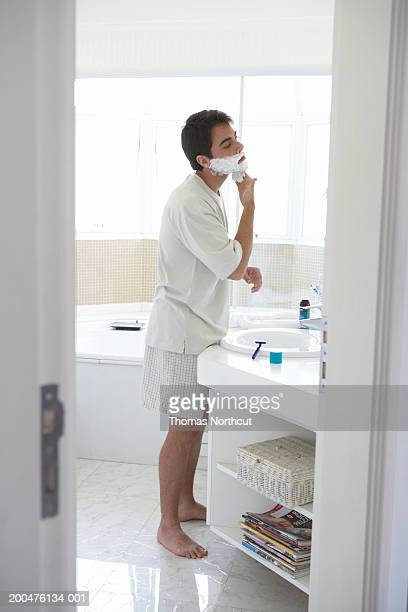Man applying shaving cream to face in bathroom mirror, side view