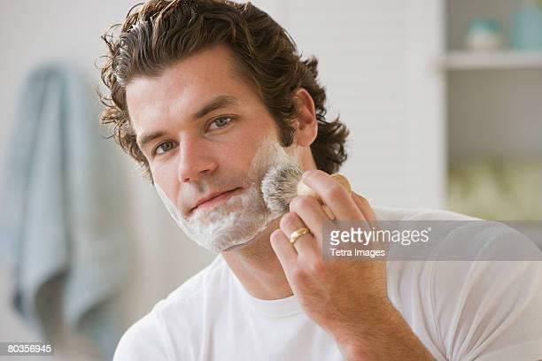 Man applying shaving cream to face