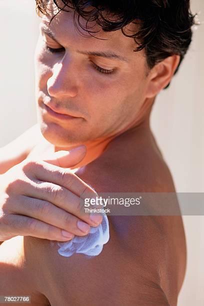 Man applying skin lotion