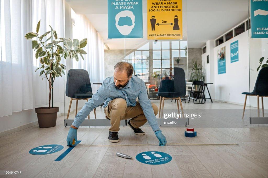 Man applying social distancing sign at office : Stock Photo