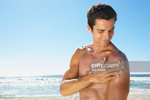 Mann anwenden Sonnenschutz und Sonnencreme im Freien