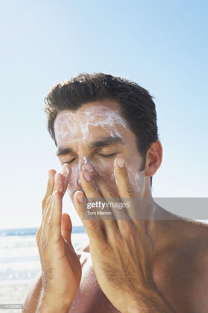 Man applying sun block or suntan lotion to face : Stock Photo