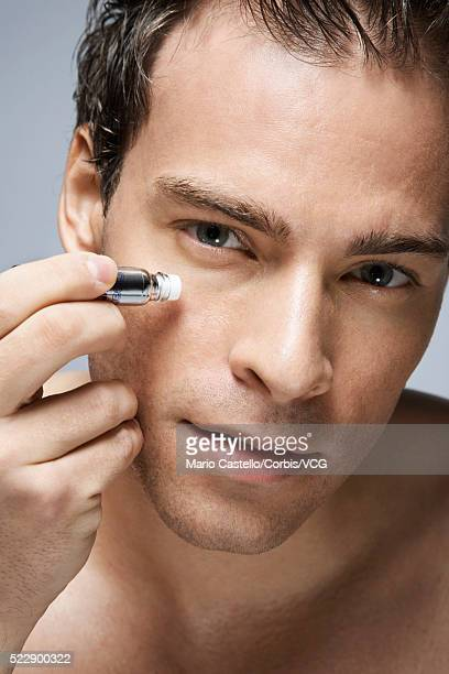 man applying wrinkle cream under his eyes - metrosexual stock pictures, royalty-free photos & images