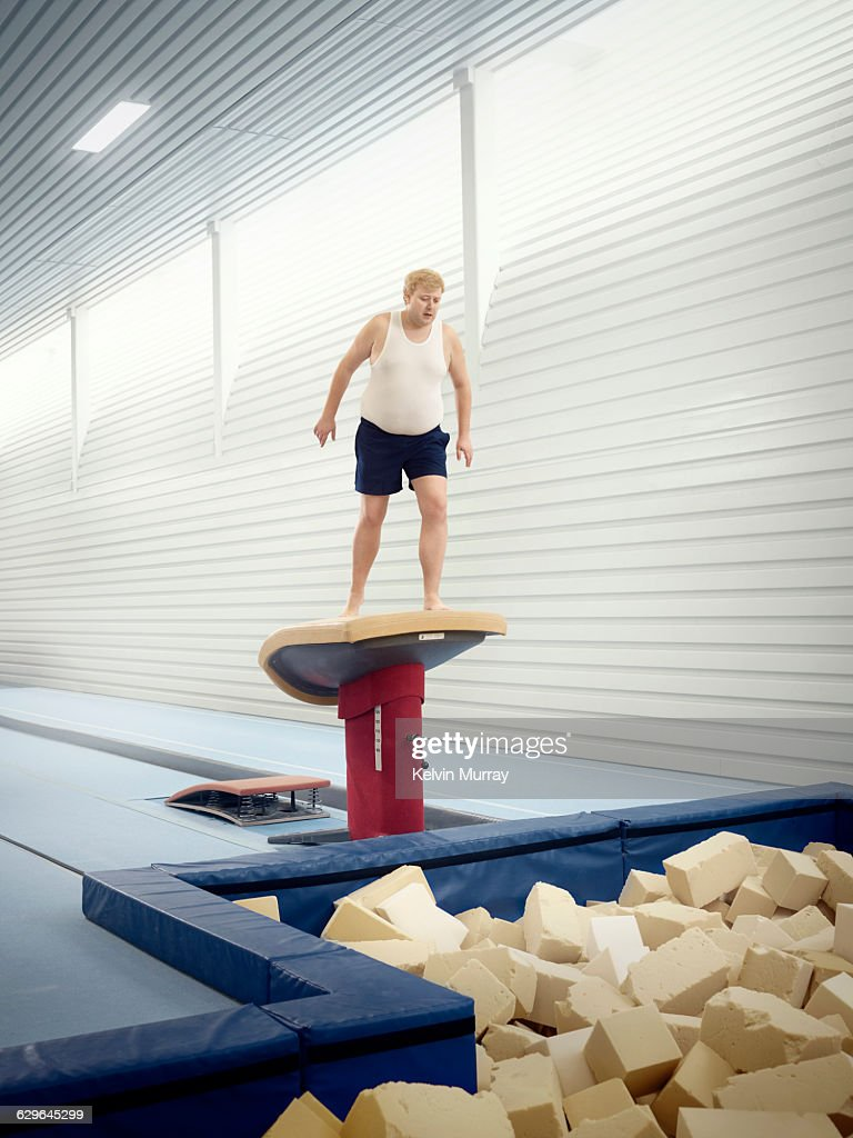 Man apprehensively looks in to foam pit in gym : Stock Photo