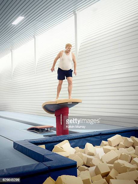 Man apprehensively looks in to foam pit in gym