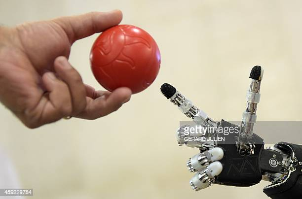 A man approaches a plastic ball toward the finger of humanoid robot iCub during the 2014 IEEERAS International Conference on Humanoid Robots in...