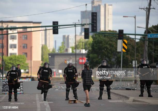 A man approaches a police line after a night of protests and violence on May 29 2020 in Minneapolis Minnesota The National Guard has been activated...