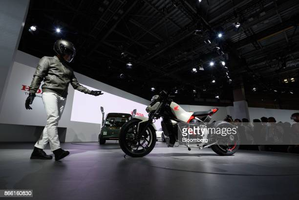 A man approaches to a Honda Motor Co Riding Assiste motorcycle on stage during an unveiling ceremony at the Tokyo Motor Show in Tokyo Japan on...