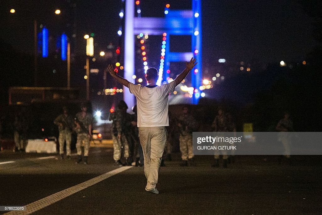 A man approaches Turkish military with his hands up at the entrance to the Bosphorus bridge in Istanbul on July 16, 2016. Turkish security forces on July 15 partially shut down the two bridges across the Bosphorus Strait in Istanbul. Turkish military forces on July 16 opened fire on crowds gathered in Istanbul following a coup attempt, causing casualties, an AFP photographer said. / AFP / GURCAN
