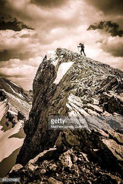 Man approaching summit peak with dramatic clouds in background