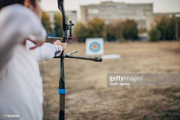 man archer aiming at target outdoors - longbow stock pictures, royalty-free photos & images