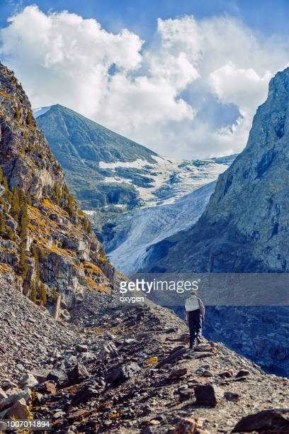man are going to the side glacier small aktru. altai republic. russia - summits russia 2015 stock pictures, royalty-free photos & images