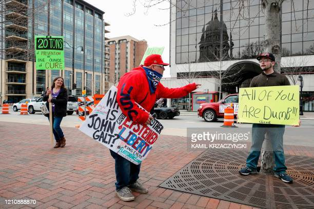 A man argues with a protester against the coronavirus shutdown in front of State Capitol in Madison Wisconsin on April 24 2020 Gyms hair salons and...