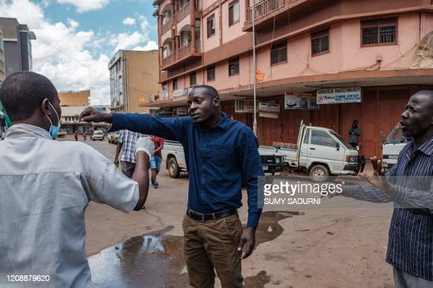 A man argues with local community volunteers about washing his hands before entering Nakasero market in Kampala on April 1 2020 Ugandan President...