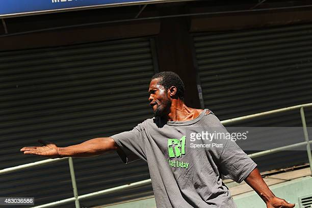 """Man argues with police in an area where people smoke K2 or """"Spice"""", a synthetic marijuana drug, in East Harlem on August 5, 2015 in New York City...."""