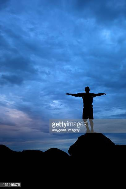Mann Arme sich unter dramatischen Sonnenuntergang-Himmel